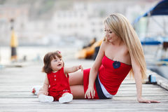 Mother And Daughter Having Fun Outside On The Dock Stock Photo