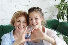 Mother And Daughter Love. Adult Woman And Young Woman Stacking Hands In Heart Sign Looking At Camera. Stock Photography