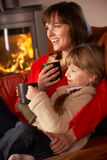 Mother And Daughter Relaxing With Hot Drink Royalty Free Stock Images