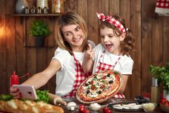 Mother And Daughter Taking Selfie With Pizza On Smartphone Royalty Free Stock Photography