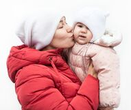 Mother And Daughter Wearing Cold-weather Clothing Standing On White Background, Mom Kissing Her Baby While Holding In Arms Royalty Free Stock Photography