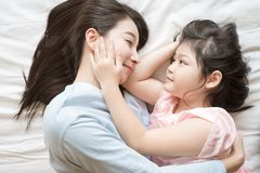 Free Mother And Her Daughter Child Girl Hugging And Stroking Her Mom In The Bedroom .Happy Asian Family. Royalty Free Stock Photo - 153508165
