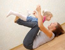Mother And Her Little Daughter On Wooden Floor Royalty Free Stock Photography