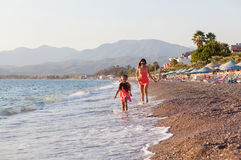 Mother And Her Little Daughter Playing And Running On The Beach