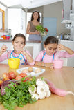 Mother And Twins Beating Eggs In Kitchen Stock Photo
