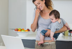 Mother answering cellphone while carrying baby Royalty Free Stock Images