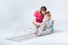 Mother appeasing crying daughter during training Stock Image