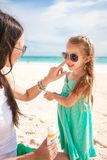 Mother apply sunblock cream on her little child Stock Photo