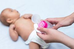 Mother is applying baby powder to her newborn stock image