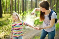Free Mother Applying Insect Repellent To Her Daughter Before Forest Hike Summer Day. Protecting Children From Biting Insects At Summer Stock Photo - 176478570