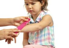 Mother applying kinisiology tape to her daughter injury hand royalty free stock image