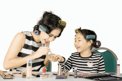 Mother applying nail polish to her daughter. Pretty mother doing makeup while applying nail polish to her daughter,  on white background Stock Photography