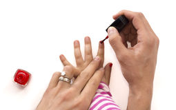 Mother applying nail polish to her little girl isolated Royalty Free Stock Image