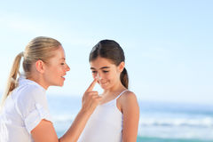 Mother applying sun cream on her daugter's nose Stock Photo