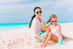 Young mother applying sun cream to daughter nose on the beach. Sun protection
