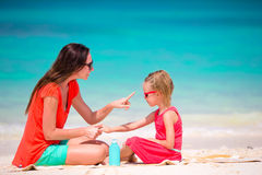 Mother applying sun protection cream to her daughter at tropical beach Royalty Free Stock Image