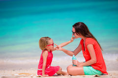 Mother applying sun protection cream to her daughter at tropical beach Stock Images