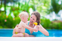 Mother applying sun screen on baby in swimming pool. Young mother and cute baby boy enjoying summer vacation in a tropical resort at a swimming pool, parent Stock Photos
