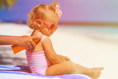 Mother applying sunblock cream on daughter shoulder. Parent applying sunblock cream on daughter shoulder, sun protection Royalty Free Stock Photo