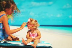Mother applying sunblock cream on daughter shoulder. Sun protection Stock Image
