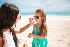 Mother applying sunblock cream on her child nose Royalty Free Stock Photos