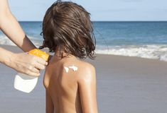 Mother applying sunblock cream with spray gun to her daughter on stock images