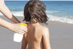 Mother applying sunblock cream with spray gun to her daughter on stock photography