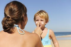 Mother applying sunscream to her daughter. Suncare on the beach: Mother applying sunscream to her daughter Stock Photo