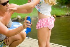 Mother Applying Sunscreen. A woman spraying sunscreen onto a young girl Stock Image