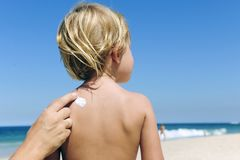Mother applying sunscreen on child�s back Royalty Free Stock Images
