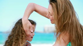 Mother applying sunscreen on a little girl. On the beach stock video footage