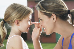 Mother Applying Sunscreen To Girl S Nose Royalty Free Stock Photo
