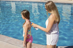 Mother applying sunscreen to little girl at the pool Stock Image