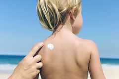 Mother applying suntan lotion on child�s back Stock Photo
