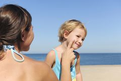 Mother applying suntan lotion to her daughter. Suncare on the beach: Mother applying suntan lotion to her daughter Royalty Free Stock Photography