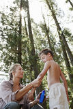 Mother Applying Suntan Lotion To Son In Forest Stock Image