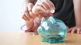Mother and Asian little girl putting money coin to clear piggy bank select focus on piggy shallow depth of field.  stock video