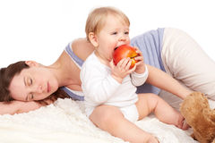 Mother is asleep and child eats. Mother is asleep and child stock photo