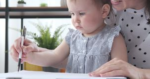Mother assisting baby daughter to draw on paper stock video footage