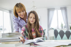 Mother assisting daughter in doing homework at table Royalty Free Stock Photo
