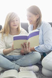 Mother assisting daughter in homework at home Stock Photography