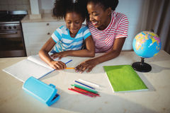Mother assisting daughter with homework Royalty Free Stock Photos