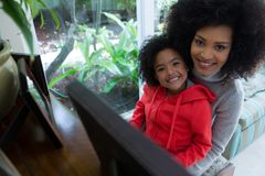 Mother assisting daughter in playing piano Stock Image