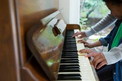 Mother assisting daughter in playing piano Stock Photo
