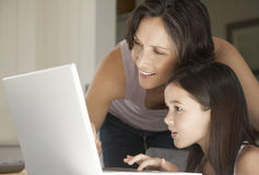 Mother Assisting Daughter In Using Laptop Stock Images