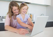 Mother assisting daughter in using laptop at table Stock Photo