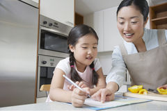 Mother Assisting Girl With Homework Stock Photography