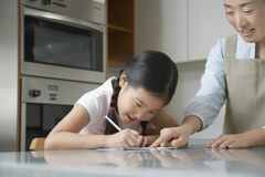Mother Assisting Girl With Homework Stock Images