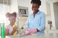 Mother assisting her daughter in cleaning utensils. At home Stock Photos