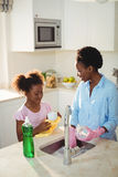 Mother assisting her daughter in cleaning utensils. At home Stock Photo